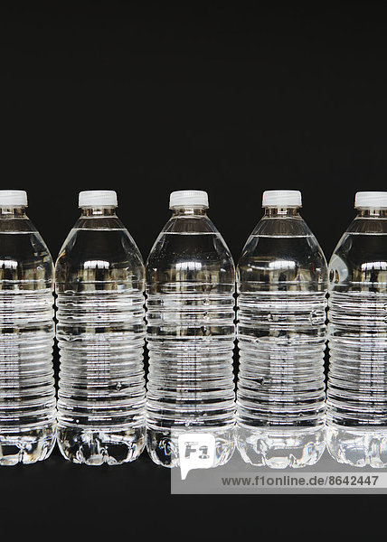 Reihe klarer Plastik-Wasserflaschen  die mit gefiltertem Wasser gefüllt sind