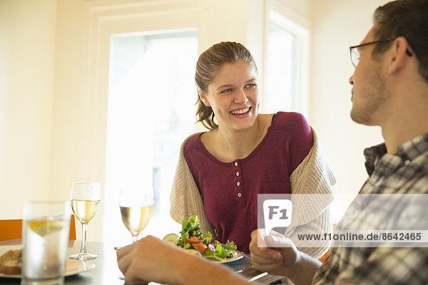 Ein junger Mann und eine junge Frau sitzen zusammen bei einer Mahlzeit und trinken Wein.