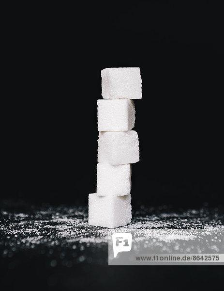 Stapel von Zuckerwürfeln  übereinander balancierend  auf schwarzem Hintergrund