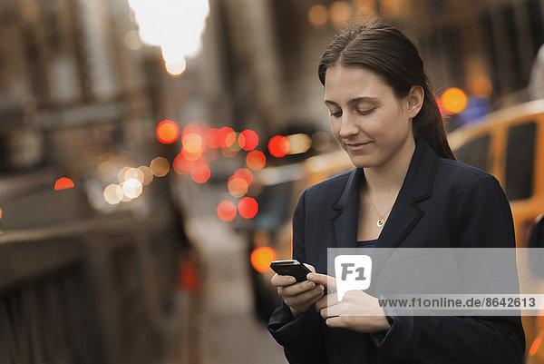 Eine Frau in einer Business-Jacke  die in der Abenddämmerung auf einem Bürgersteig in der Stadt ihr Handy überprüft.