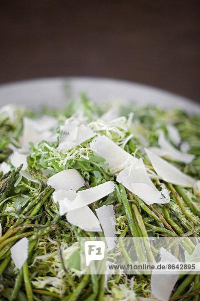 Biologisch zubereitetes Gemüsegericht für eine Party. Bauernstand. Gegrillter Spargel und Frisesalat. Parmesankäse-Splitter.