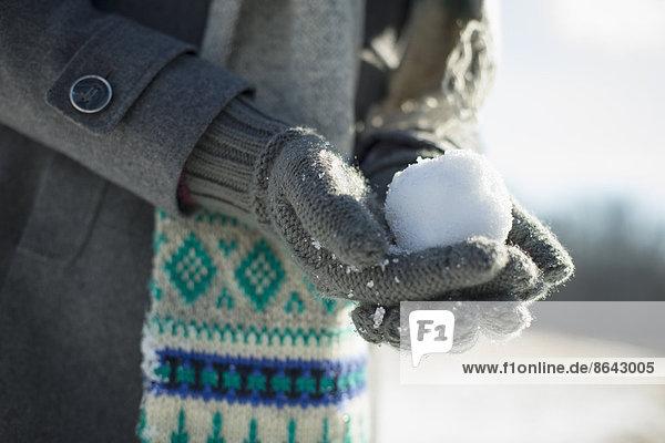 Eine junge Frau  die einen kleinen Schneeball in ihren behandschuhten Händen hält.