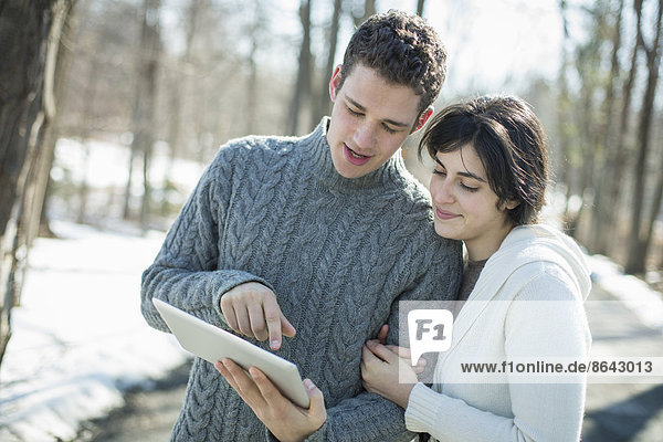 Ein Paar  das sich ein Computertablett ansieht. Eng beieinander stehend an einem Wintertag im Wald.