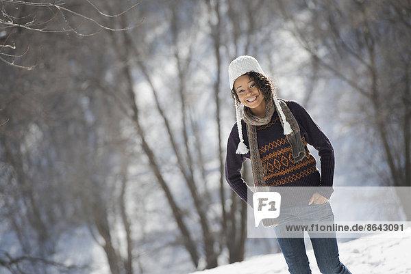 Winterlandschaft mit Schnee auf dem Boden. Eine junge Frau mit Wollmütze.