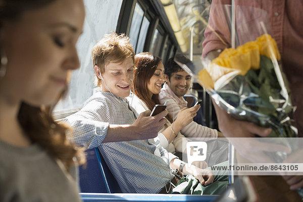 Urbaner Lebensstil. Eine Gruppe von Menschen  Männer und Frauen  in einem Stadtbus in New York City. Zwei Personen überprüfen ihre Smartphones.