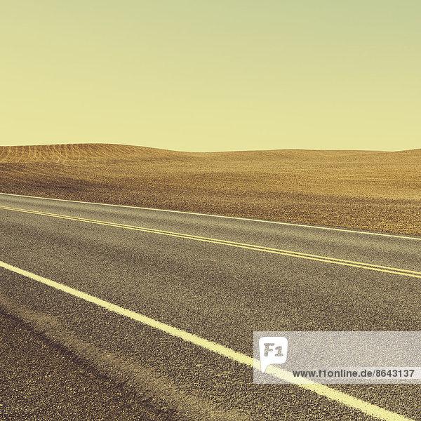 Eine Straße durch die landwirtschaftliche Landschaft aus gepflügten Feldern und Ackerland in der Nähe von Pullman im Bundesstaat Washington.