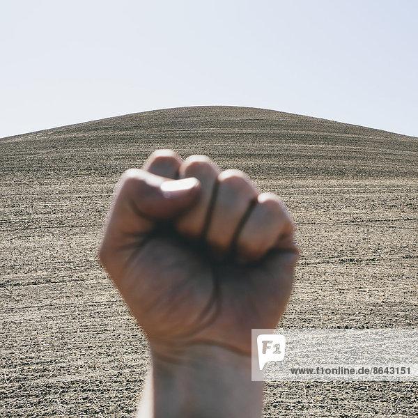 Eine gebündelte Hand  die eine Faust macht und eine Geste macht. Im Hintergrund ein gepflügtes Feld und Ackerland in der Nähe von Pullman im Bundesstaat Washington.
