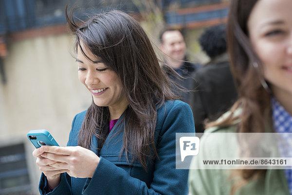 Eine Frau  die ihr türkisfarbenes Smartphone überprüft  unter anderen Menschen auf einer Straße in der Stadt.
