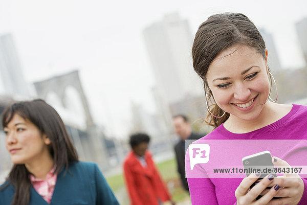 New York City  die Brooklyn Bridge  die über den East River führt. Vier Freunde im Park am Fluss  eine Frau  die auf ihr Telefon schaut und lächelt.