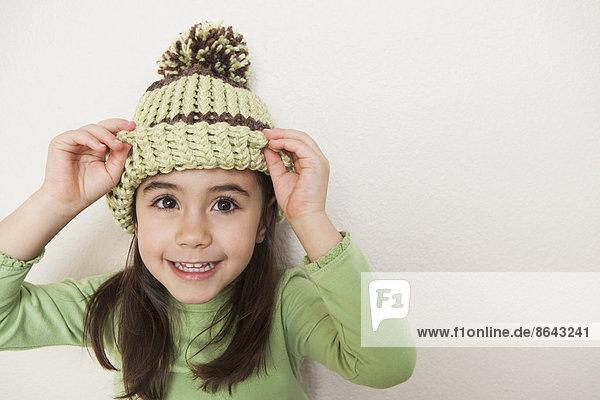 Ein kleines Kind mit langen braunen Haaren  das eine Strickmütze mit Pompon trägt und von unten unter der Krempe hervorschaut.