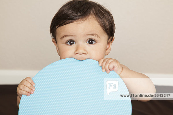 Ein junger  8 Monate alter Junge  der Stoffwindeln trägt  eine große blaue Scheibe hält und auf dem Rand kaut. Ein junger, 8 Monate alter Junge, der Stoffwindeln trägt, eine große blaue Scheibe hält und auf dem Rand kaut.