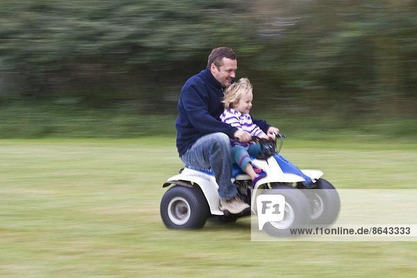 Kleinkind mit Vater auf Scooter