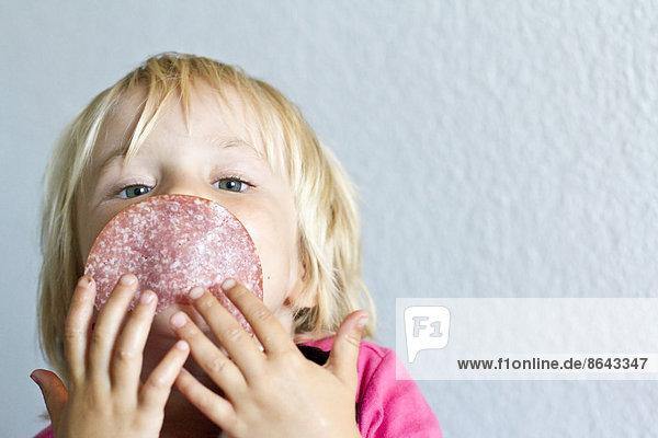 Blondes Mädchen hält sich eine Salami-Scheibe vor das Gesicht  Portrait Blondes Mädchen hält sich eine Salami-Scheibe vor das Gesicht, Portrait