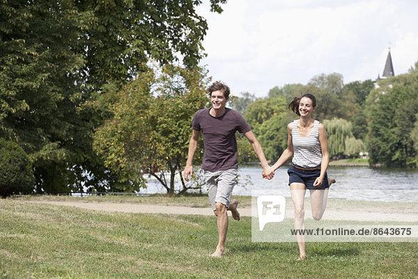 Junges Paar hält sich an den Händen und läuft im Park.