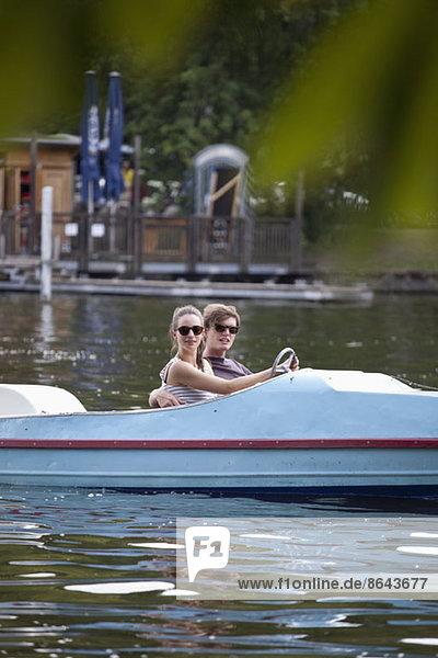Junges Paar beim Tretbootfahren auf dem See