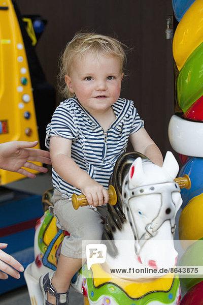 Baby Junge reitet auf einem Vergnügungspferd