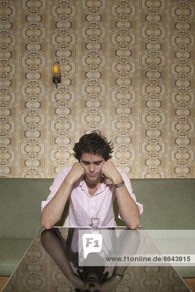 Ein depressiver Mann  der auf ein Schnapsglas schaut.