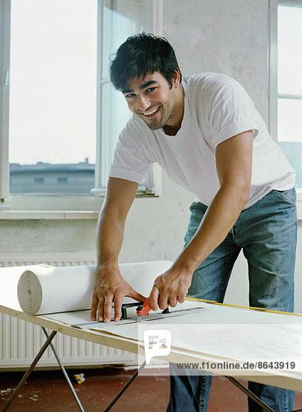 Ein Mann schneidet Papier mit Arbeitsgerät  Portrait