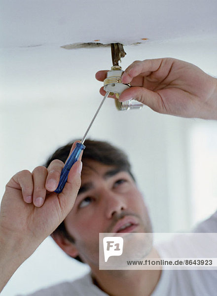 Ein Mann  der ein Licht repariert.