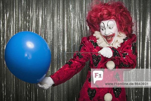 Ein Clown macht sich bereit  einen Ballon mit einer Nadel zu knallen.