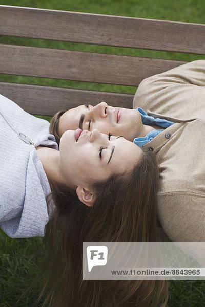 Junges Paar schläft auf der Bank