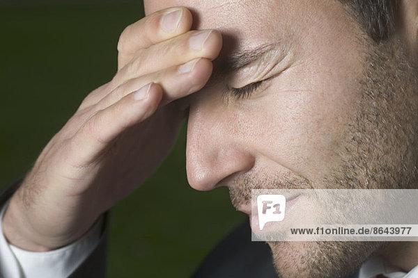Junger Mann mit Kopfschmerzen  Nahaufnahme