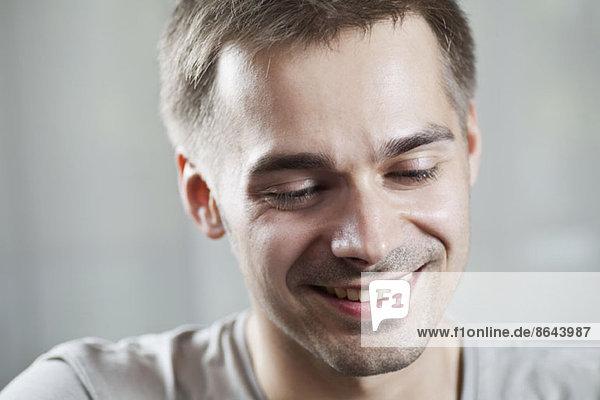 Junger Mann schaut hinunter und lächelt  Nahaufnahme