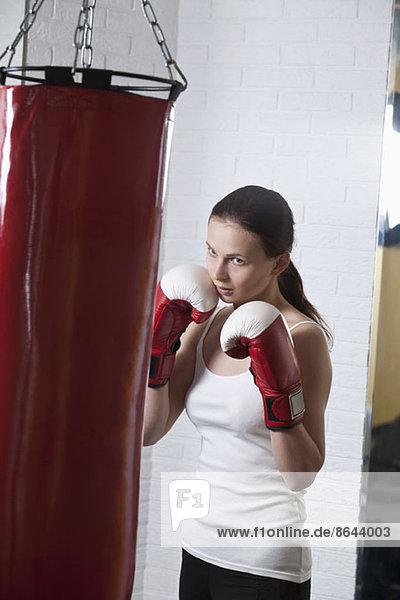 Junge Frau schlägt Boxsack