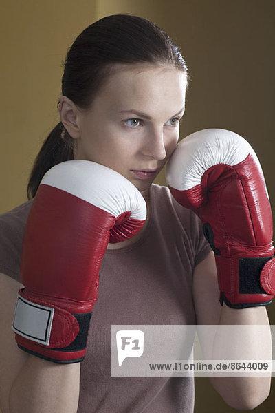 Junge Frau im Boxhandschuh  wegschauend