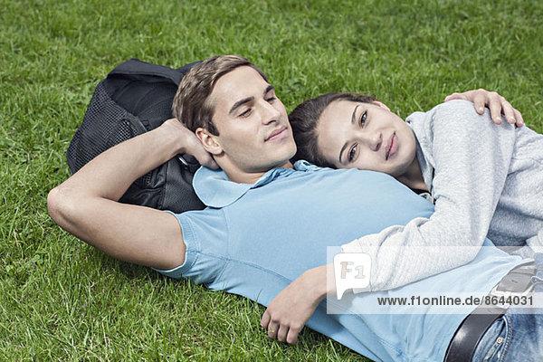 Junges Paar auf Gras liegend