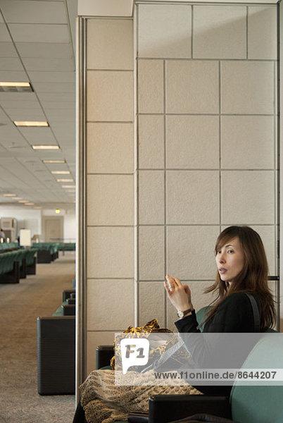 Eine Frau sitzt auf einem Sofa im Wartezimmer.