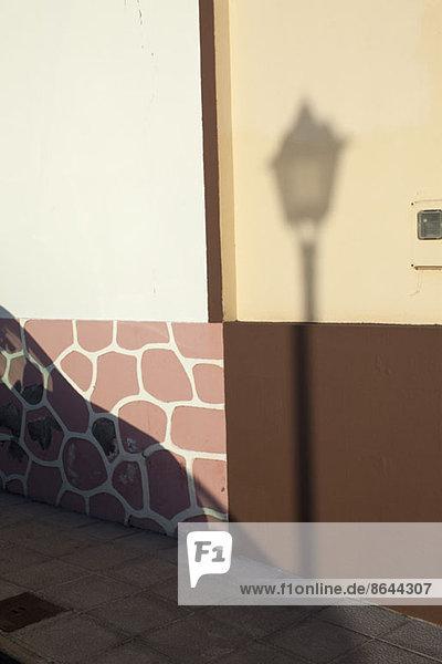 Schatten der Straßenbeleuchtung an der Wand
