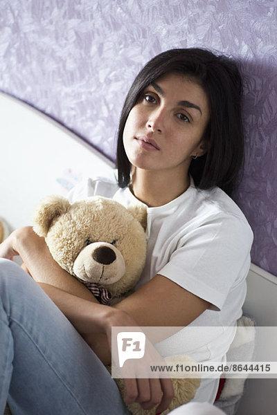 Frau kuschelt Teddybär im Bett