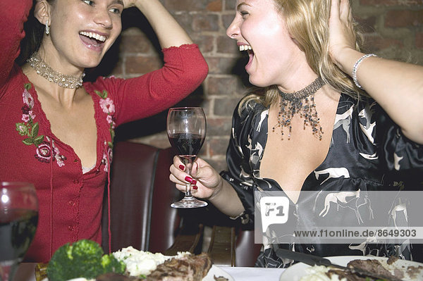 Two mid adult women enjoying night out in restaurant