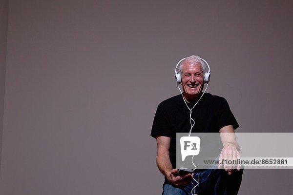 Porträt eines älteren Mannes  der den MP3-Player über Kopfhörer hört.