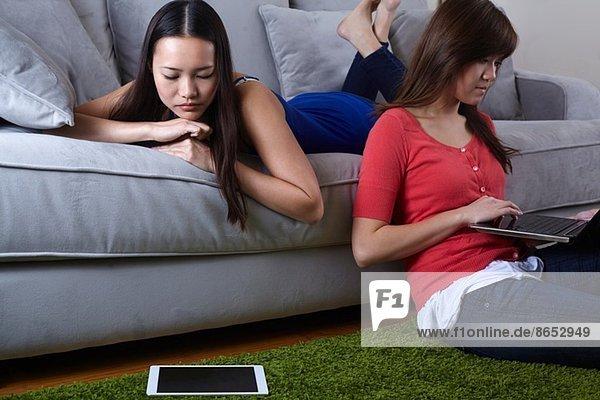 Zwei junge Frauen im Wohnzimmer mit digitalen Tabletten