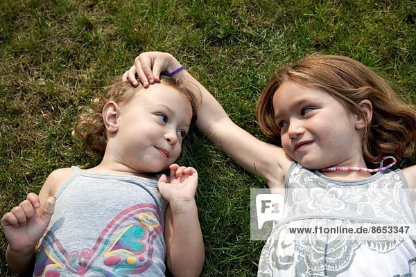 Porträt zweier junger Schwestern auf Gras liegend