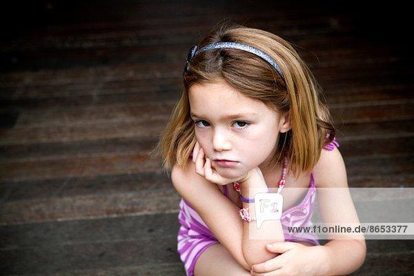 Mürrisches junges Mädchen sitzt auf der Veranda mit Händen am Kinn.