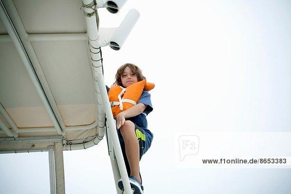 Junge in Schwimmweste klettert die Bootsstufen hinauf