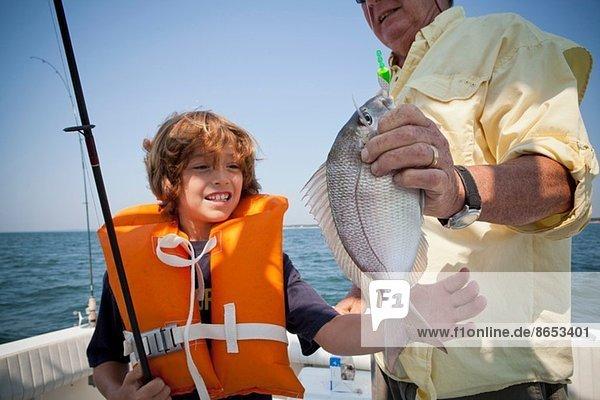 Junge und Großvater mit gefangenem Fisch auf dem Boot  Falmouth  Massachusetts  USA