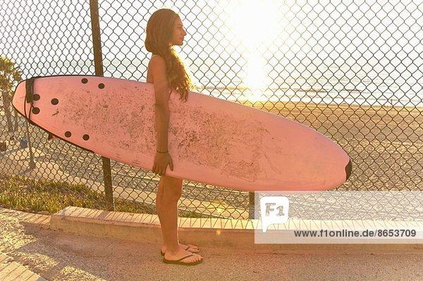 Mädchen am Strand stehend mit rosa Surfbrett Mädchen am Strand stehend mit rosa Surfbrett