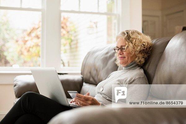 Senior Frau online einkaufen auf dem Laptop