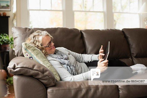 Seniorin entspannt auf dem Sofa mit digitalem Tablett
