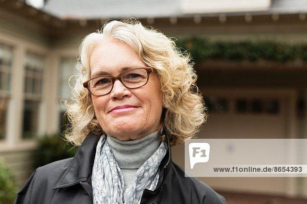 Porträt einer glücklichen Seniorin vor dem Haus
