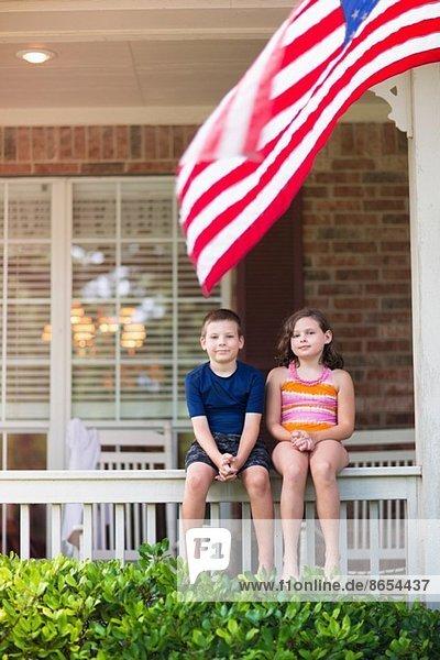 Geschwister auf der Veranda sitzend