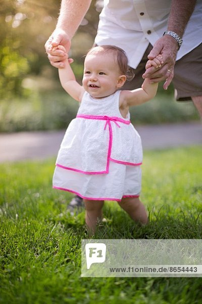 Grandfather helping granddaughter to walk