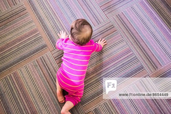 Toddler girl crawling on floor  overhead view