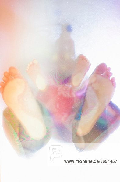 Toddler and adult's bare feet  low angle view