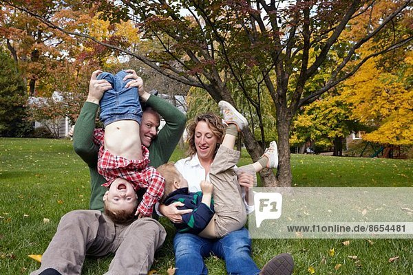 Mittlere erwachsene Eltern und junge Söhne beim Spielen im Garten