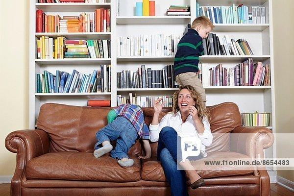 Mutter und kleine Söhne beim Spielen auf dem Sofa